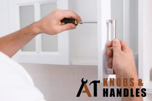 handle-on-white-cabinet-being-screwed-door-knob-handle-installation-a1-knobs-&-handles-singapore